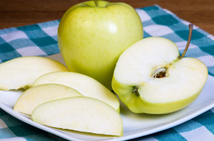 yellow apple and apple slices on a plate