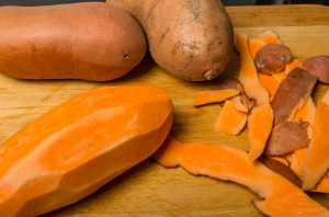 Whole yams being peeled with peels