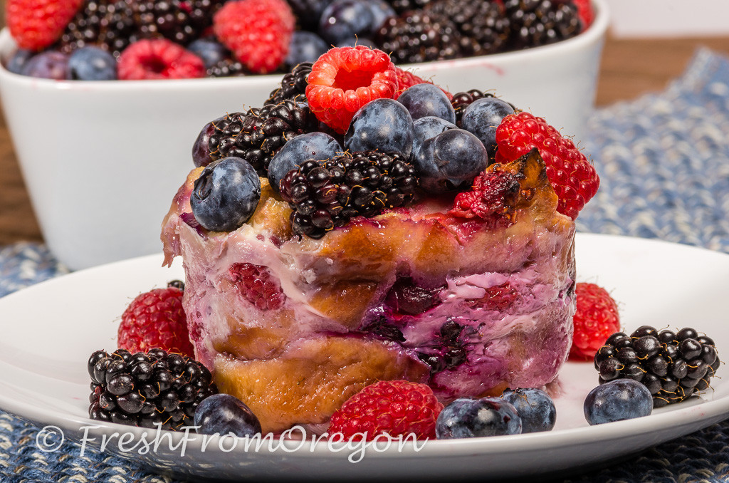 Mixed berry bread pudding with blueberries, blackberries and red raspberries on a white plate